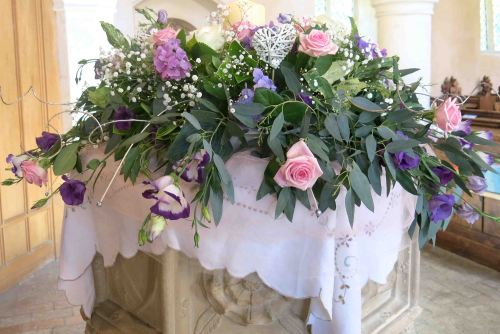 Flowers with a candle on the font