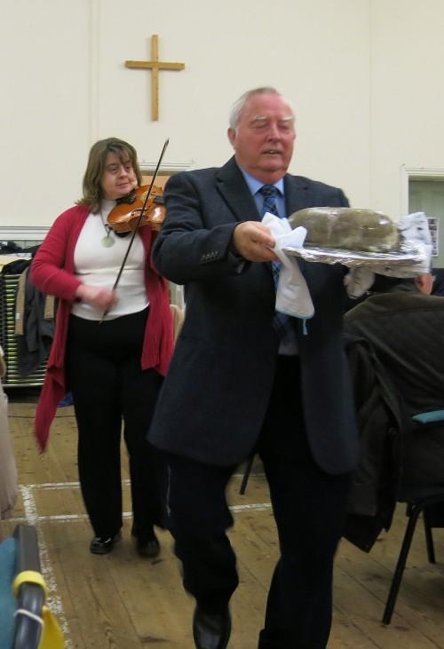 Elaine fiddles while David bears the haggis.